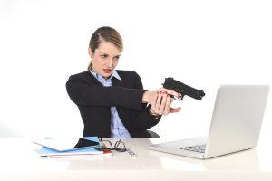 young lady aims gun at laptop